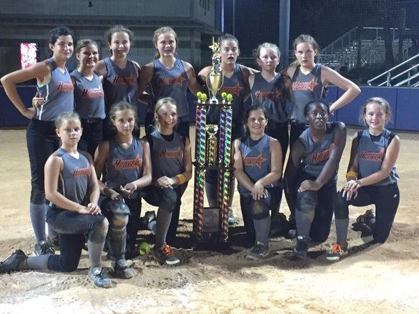 Image of girls youth softball team sitting and standing around trophy
